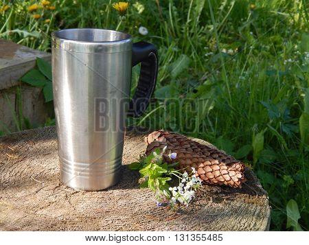 Mug of tea on a stump with wildflowers