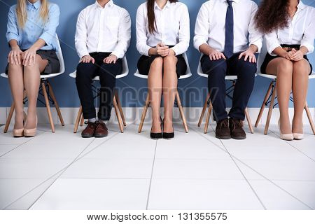 Young people sitting on a chairs in blue hall, close up