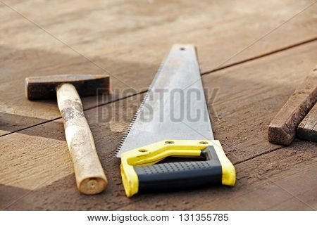 Hammer and saw on wooden floor