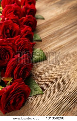 Bouquet of beautiful red roses on wooden background