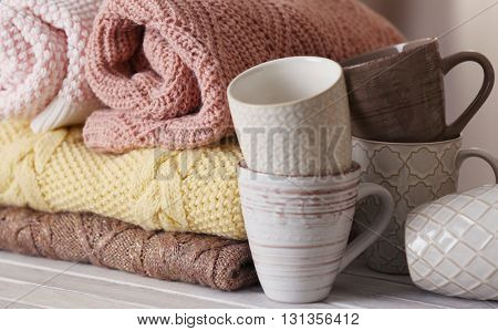 Stack of knitted clothes and cups on wooden table indoors