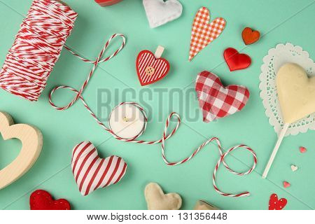 Valentine's Day concept. Handmade hearts on turquoise background, close up