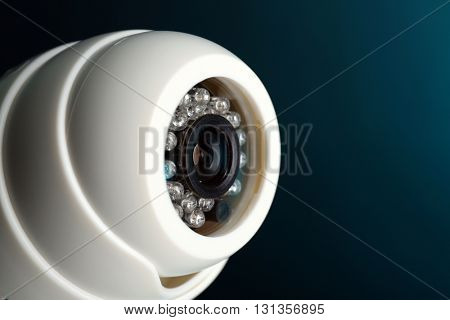 Security CCTV camera on blue background, closeup