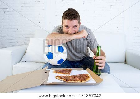 young man alone holding ball and beer bottle in stress watching football game on television sitting at home living room sofa couch with pizza box enjoying the match excited biting his arm nervous