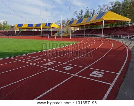 Running track on the sport stadium with covered grandstand