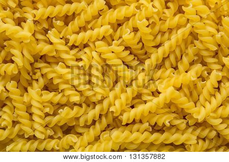 dry curly egg noodles, close-up background in large quantities