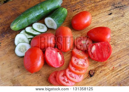 Fresh colorful tomatoes and cucumbers whole and sliced on a rustic table top