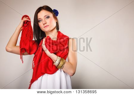 Pretty summer woman fashionable girl in white dress with red shawl on gray background. Fashion photo