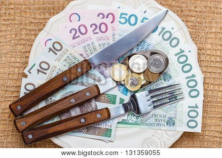 Cost of living price of eating food budget concept. Polish money on kitchen table plate with banknotes cutlery