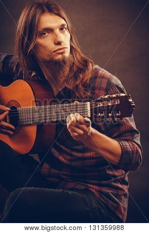 Music hobby concept. Focused hippie with his guitar.