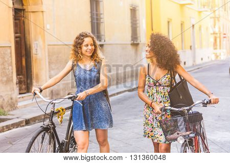 Multiracial Couple Of Friends With Bikes In The City