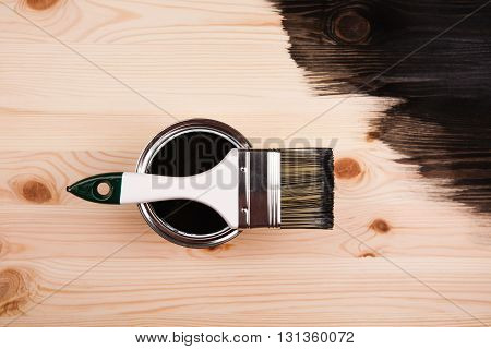 Paint brush on the can lying on wooden background. The surface is half - toned with red color.
