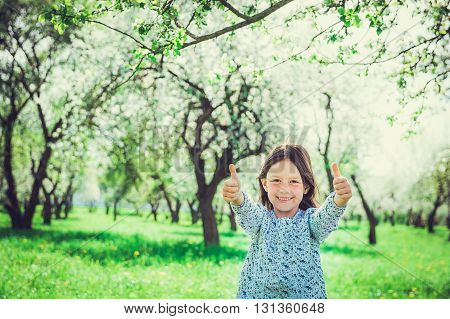 Smiling girl in the garden, showing hands ok. Child in spring fruit orchard.