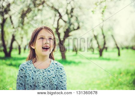 Portrait of surprised beautiful little girl in the garden with open-mouthed and looking up. Child in spring fruit orchard.