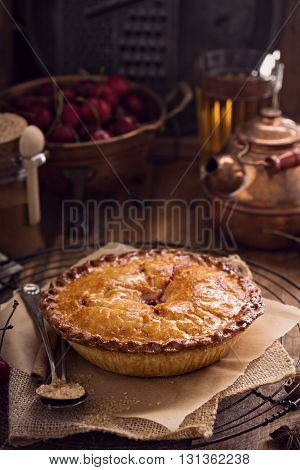Cherry pie with cinnamon and brown sugar on rustic background