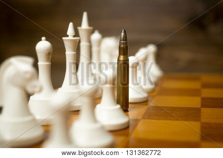 Conceptual photo of bullet in row of white pawns. Concept of military conflict