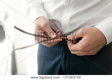 Closeup photo of young businessman getting dressed and fastening leather belt on trousers