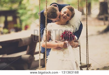 Toned portrait of young groom kissing bride sitting on swing at park