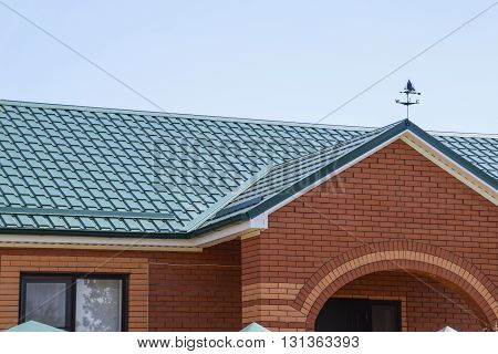 Facade Of A Brick Building With A Green Roof Made Of Metal.