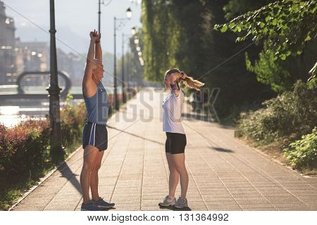 jogging couple warming up and stretching before morning running training workout  in the city with sunrise in background