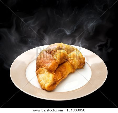 Fresh and hot croissant on ceramic plate