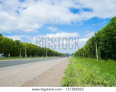 Road With Moving Cars And Green Surroundings On The Sides
