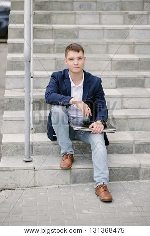 Portrait of a young businessman sitting with notebook on stairs. Man in blue jacket and white polo on the street.