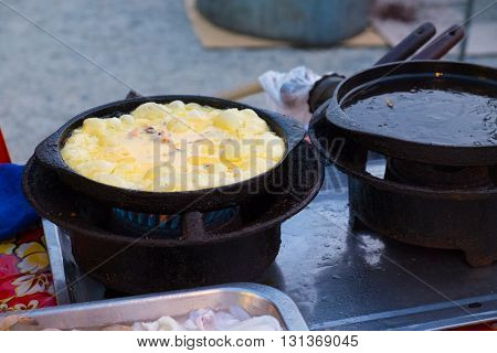 Fried mussel pancakes in big iron frying pan / Tasty fried mussel pancakes (Thai food) in a cast-iron pan