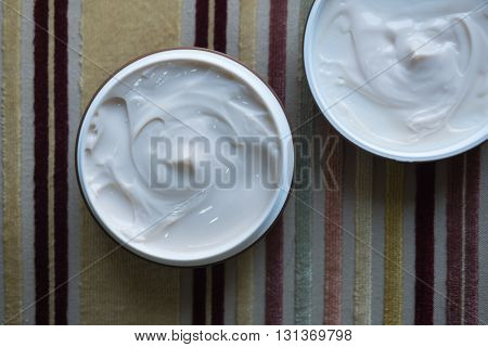 Hair wax and clay in tubs, top view