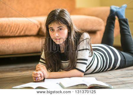 Teen girl studying lying on the floor.