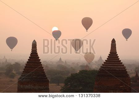 air balloons over Buddhist temples at sunrise. Bagan, Myanmar.
