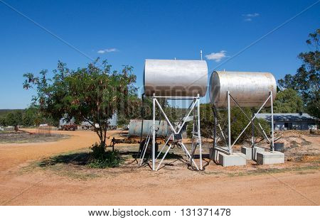 Two elevated fuel tank barrels on metal frames in farmland with generic vegetation under a blue sky with clouds in Western Australia.