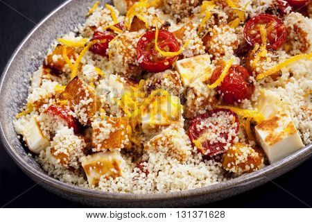 Couscous with roasted pumpkin, tomatoes and grilled halloumi cheese, topped by orange zest.