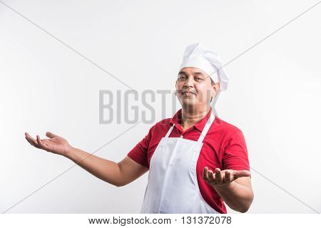 Portrait of handsome Indian male chef in uniform hands showing something and smiling, standing on plain white background, copy space at side. asian male chef presenting