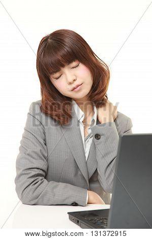studio shot of Japanese businesswoman suffers from neck ache