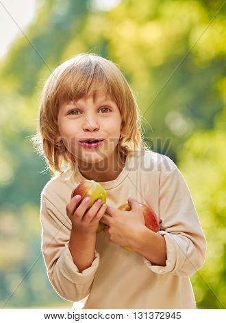 portrait of little handsome boy clasps apples by hands, outdoor summer autumn warm