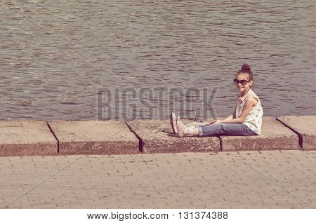 little girl in big sunglasses sitting on the river embankment