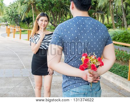 Young Man Hiding Roses From His Back And Give Them To His Girlfriend