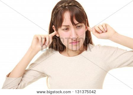 Young woman suffers from noise  on white background