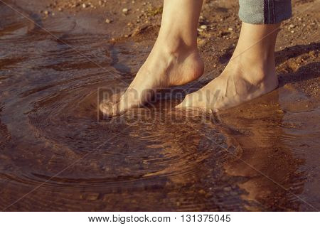 woman's feet standing in the water on the sand