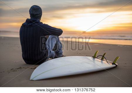 A surfer with his surfboard at the sunset looking to the waves