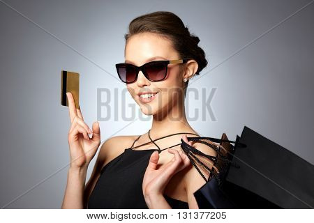 sale, finances, fashion, people and luxury concept - happy beautiful young woman in black sunglasses with credit card and shopping bags over gray background
