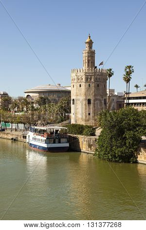 Ancient lighthouse Torre del Oro at Seville, a tourist boat anchored at the pier