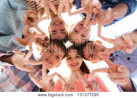 childhood, fashion, friendship and people concept - happy smiling children showing peace hand sign and standing in circle