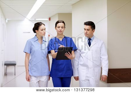 clinic, profession, people, health care and medicine concept - group of medics or doctors with clipboard walking along hospital corridor