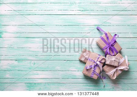 Many festive gift boxes with presents on turquoise wooden background. Selective focus. Place for text.