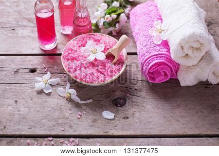 Spa products. Sea salt in bowl towels aroma oil in bottles and flowers on vintage wooden background. Selective focus.
