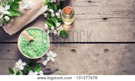 Border from spa products. Sea salt in bowl towels aroma oil in bottles and flowers on vintage wooden background. Selective focus. Falt lay with copy space. Toned image.