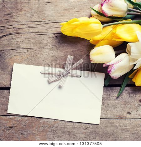 Bright yellow and white spring tulips and empty tag on vintage wooden background. Selective focus. Place for text. Flat lay. Square image. Toned image.