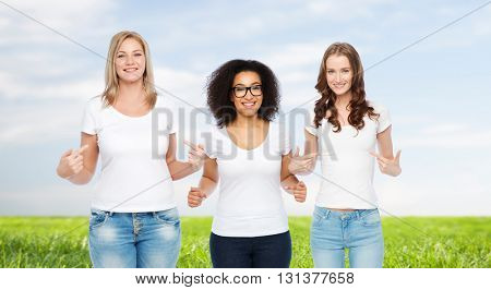 friendship, diverse, body positive and people concept - group of happy different size women in white t-shirts pointing finger to themselves over blue sky and grass background